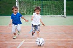 两小男孩,踢橄榄球 库存照片