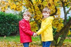 两小的最好的朋友和孩子男孩秋天在五颜六色的衣裳停放 免版税图库摄影