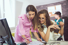 两少妇在研究一个创造性的设计的办公室 免版税库存照片