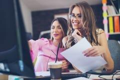 两少妇在研究一个创造性的设计的办公室 免版税库存图片