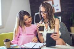 两少妇在研究一个新的创造性的设计的办公室 免版税库存照片