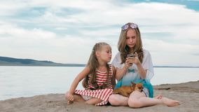 两少年坐一个沙滩,在电话的互联网上 免版税图库摄影