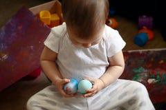 两岁儿童拿着两个复活节彩蛋 免版税库存照片