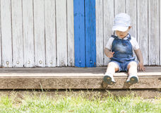 两岁的在木海滩小屋的男孩坐的画象 库存照片