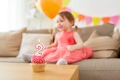 两岁的女婴的生日杯形蛋糕 库存照片