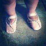 两岁的女孩佩带的芭蕾舞鞋第一次 免版税图库摄影