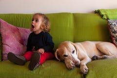 两岁的女孩和在家坐在沙发的拉布拉多猎犬 免版税库存图片