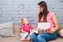 两岁的年轻母亲和女儿与明亮的印刷品的白肤金发的用途便携式计算机膝上型计算机白色坐长沙发户内 库存照片