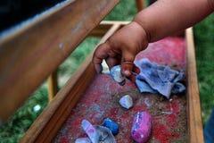 两岁的手选择蓝色白垩的女孩从各种各样的白垩 免版税库存照片
