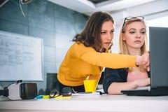 两工作在办公室和使用膝上型计算机的女商人 图库摄影