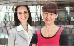两工作在办公室的可爱的妇女反对玻璃反射,企业背景 伦敦英国 库存图片
