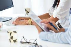 两工作在有数字式片剂的办公室的女商人 免版税库存照片