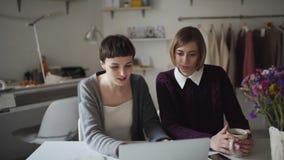 两工作在背景垂悬的衣裳的笔记本的女商人 股票视频
