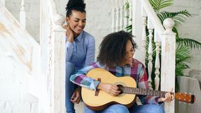 两巴西卷曲女孩sistres坐台阶和实践弹声学吉他 朋友有乐趣和唱歌 免版税库存照片