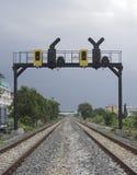 两平行的铁路通行证在有一个铁路红绿灯的一个城市 库存照片