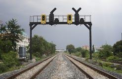 两平行的铁路通行证在有一个铁路红绿灯的一个城市 免版税图库摄影