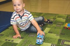两年儿童与汽车的男孩戏剧 幼儿园和幼儿园孩子的,室内操场,生活方式概念教育玩具 库存图片