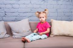 两年的一个滑稽的女孩从诞生的与白发和在一条红色衬衣和蓝色裤子在屋子里播放在长沙发的一个手机 图库摄影