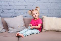 两年的一个滑稽的女孩从诞生的与白发和在一条红色衬衣和蓝色裤子在屋子里播放在长沙发的一个手机 库存图片