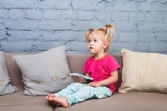 两年的一个滑稽的女孩从诞生的与白发和在一条红色衬衣和蓝色裤子在屋子里播放在长沙发的一个手机 免版税库存图片