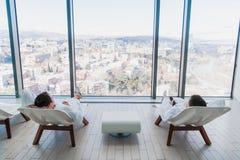 两年轻人佩带的浴巾,说谎在温泉沙龙的懒人和互相谈话在与a的一个大窗口前面 免版税库存照片