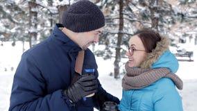 两年轻人在新鲜空气、饮料咖啡和亲吻的浪漫多雪的大气见面 影视素材