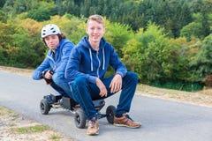 两年轻人坐mountainboard本质上 库存照片