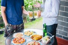 两年轻人手培养一杯啤酒庆祝假日节日愉快的饮用的啤酒户外和在家享用 免版税库存照片