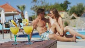 两年轻人放松在与鸡尾酒的水池 股票视频