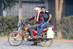两年轻印地安人坐牛奶的摩托车卖主从牛奶罐头的 印度,沃林达文, 2016年11月 免版税库存照片