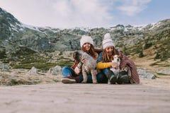两年轻女人使用与他们的狗在草甸中间 库存图片