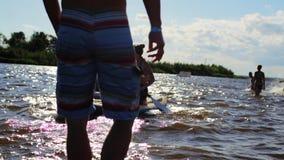 两年轻女人在一口板游泳并且漂浮在河在夏天好日子 股票视频