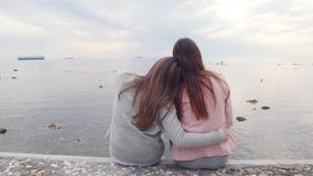 两年轻女人在海附近拥抱坐台阶看水 股票视频