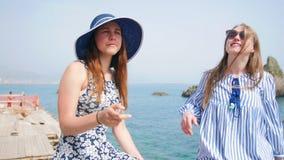 两年轻女人坐沿海岸区和谈 股票视频