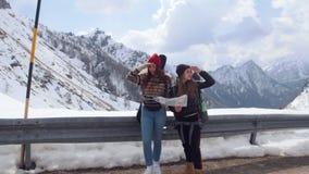 两年轻女人旅游旅行 站立在路和看在拿着在白云岩的一张地图附近与大背包 股票录像