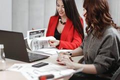 两年轻女人设计师队工作在内部开会设计项目在有膝上型计算机的书桌和 库存图片