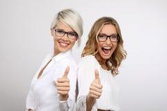 两年轻白肤金发的妇女微笑的赞许 免版税库存图片