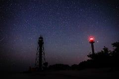 两座灯塔沙滩和海洋的剪影以满天星斗的天空为背景 免版税库存图片