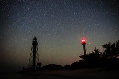 两座灯塔沙滩和海洋的剪影以满天星斗的天空为背景 库存图片