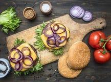 两开胃水多的家庭汉堡用牛肉、沙拉、酱瓜、乳酪和葱,蕃茄,小圆面包芝麻,在葡萄酒c 库存图片