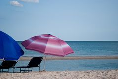 两张海滩睡椅和两把室外伞在海蓝天夏天前 库存照片