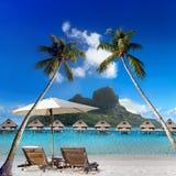 两张海滩睡椅和太阳伞在棕榈树下和海和山的看法 塔希提岛 免版税库存照片