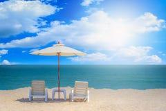 两张海滩睡椅和白色伞有蓝天背景 图库摄影