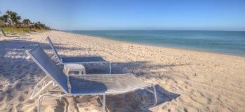 两张海滩睡椅在Lowdermilk的清楚的蓝天下靠岸 免版税库存图片