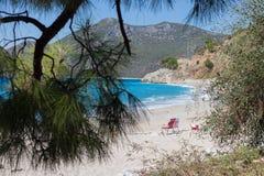两张海滩睡椅看法在Kidrak海滩的由海通过一棵针叶树 免版税库存照片