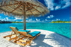 两张海滩睡椅在伞下有海景在马尔代夫 库存图片