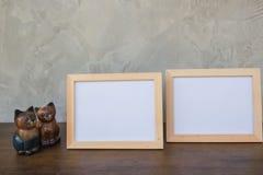 两张照片框架和玩具猫在木 免版税库存照片