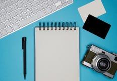 两张空白的名片大模型,纸笔记本,在空的颜色书桌上的键盘 企业空的大模型 免版税库存照片