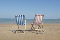 两张空的亚麻制海滩睡椅一蓝色和一红色在海滩的图象中间, facin 免版税库存照片
