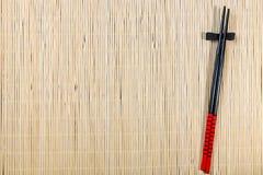 两张筷子和寿司席子 免版税库存图片